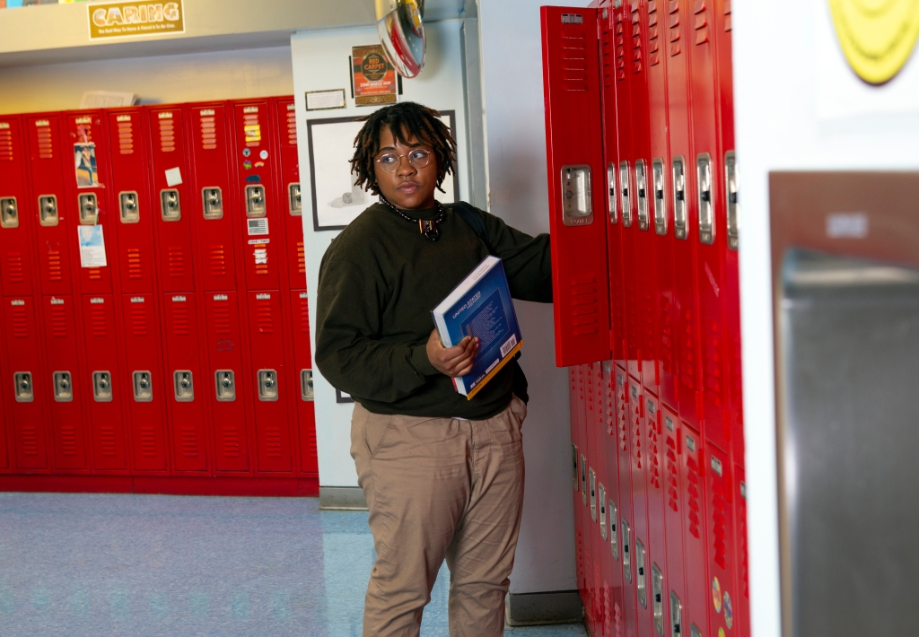 A person with ear-length dark brown hair wearing khaki pants and a dark green sweater grabs a textbook from a school hallway lined with red lockers.