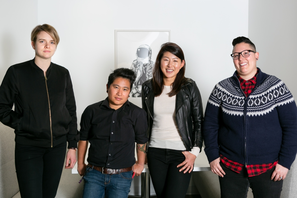 4 people stand shoulder to shoulder smiling in front of a wall with an artist depiction of an astronaut. From left to right: A tall person with short blonde hair wearing a black jacket and black pants. A shorter person with black hair styled longer on top and short on the sides wears a black button down, sleeves rolled up to show arm tattoos, and blue jeans. An average height person with chest-length dark hair tucked behind their ears, wearing a beige shirt with a black leather jacket on top and dark colored pants. An average-height person with short hair, a side fade, and glasses wears a red and black plaid shirt with a navy blue and white patterned sweater zipped on top.